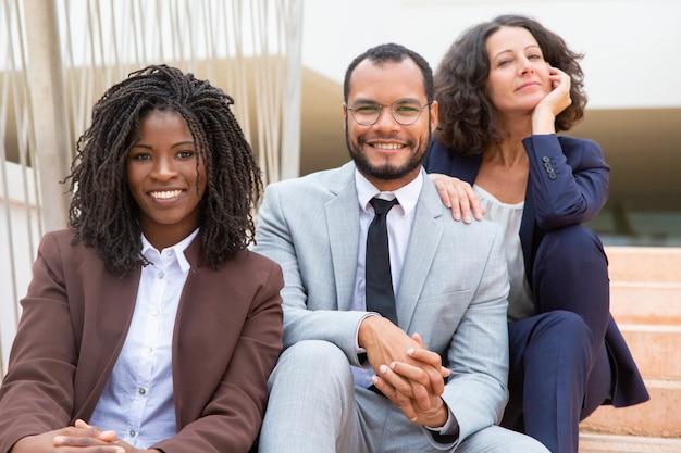 Gente di affari felice che si siede sui gradini
