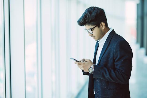 Gente di affari indiana asiatica che manda un sms facendo uso dello smartphone mentre camminando nell'ufficio moderno