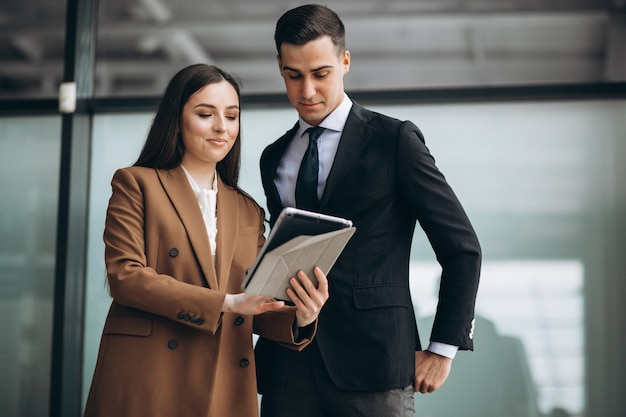 Gente di affari maschio e femminile che lavora alla compressa in ufficio
