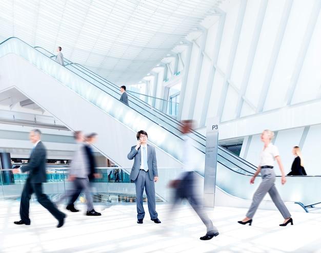 Gente di affari offuscata movimento nel centro commerciale
