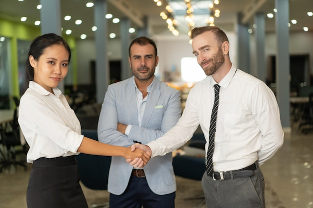 Gente di affari sicura che stringe le mani nell'ingresso dell'ufficio