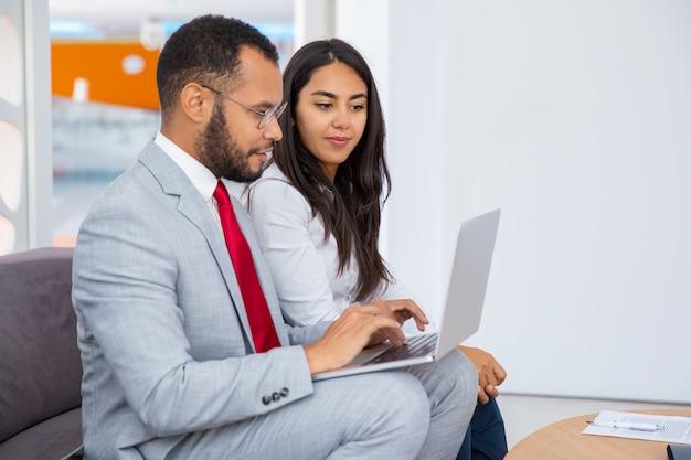 Gente di affari sorridente che per mezzo del computer portatile