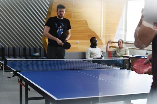Gente di affari startup che gioca insieme ping-pong durante il tempo di pausa