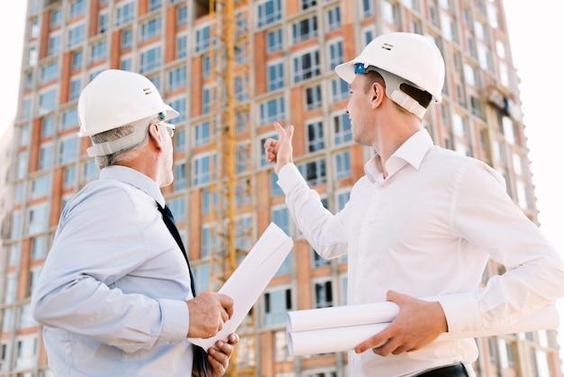 Gente di angolo basso che esamina l'impalcatura della costruzione