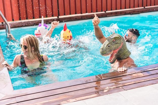 Gente felice che fa festa privata in piscina indossando maschere di animali divertenti