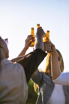 Gente felice che incoraggia con le bottiglie di birra contro il tramonto. giovani amici rilassati che si rilassano insieme nel parco. concetto di tempo libero