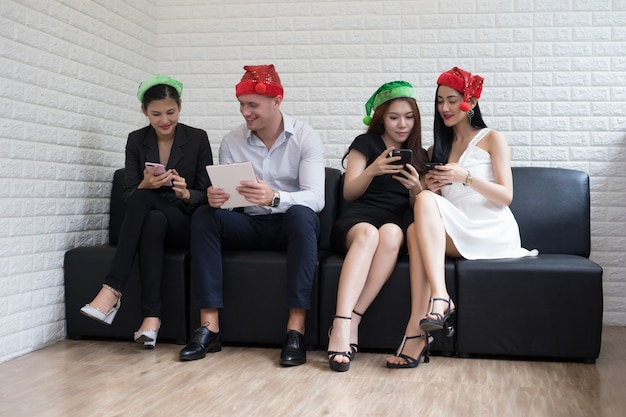 Gente felice del gruppo di affari in cappello della santa divertendosi per la festa di natale della celebrità.