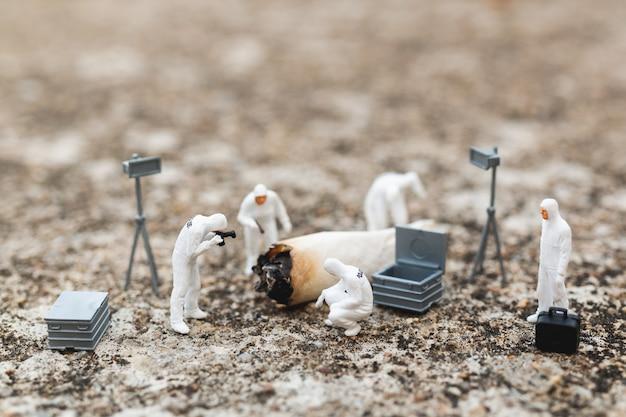 Gente in miniatura: polizia e detective che trovano prove di vecchie sigarette nella scena del crimine