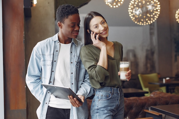 Gente internazionale in piedi in un caffè con tablet e caffè