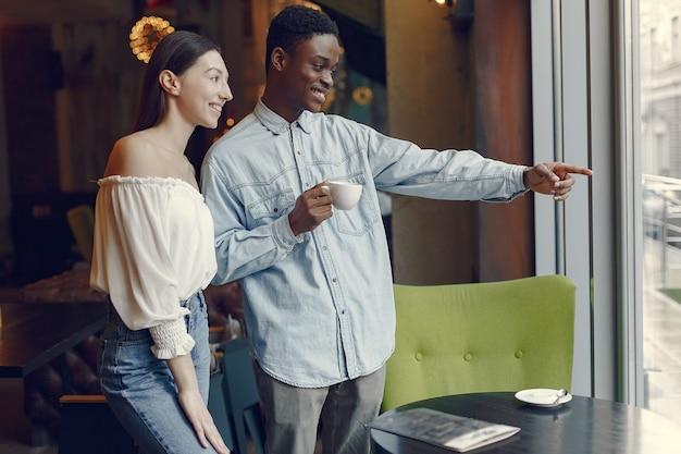 Gente internazionale in piedi in un caffè e bere un caffè