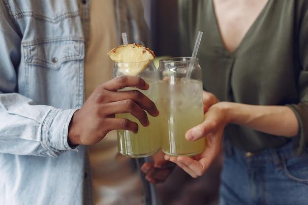 Gente internazionale in piedi in un caffè e bere un cocktail