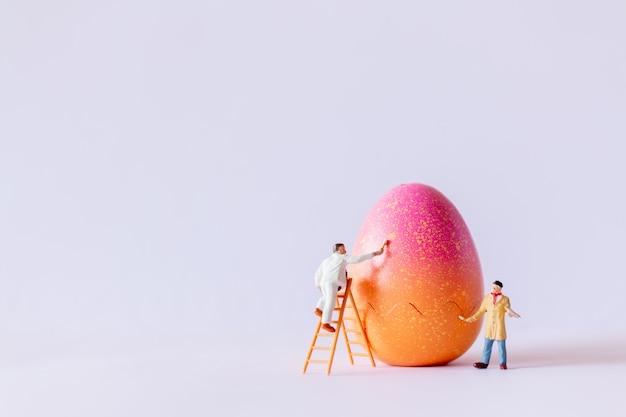 Gente miniatura che dipinge le uova di pasqua per il fondo di giorno di pasqua