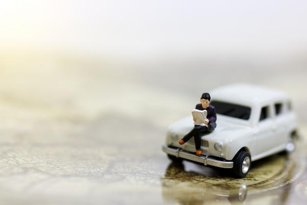 Gente miniatura che legge e che si siede sull'automobile facendo uso come del fondo.