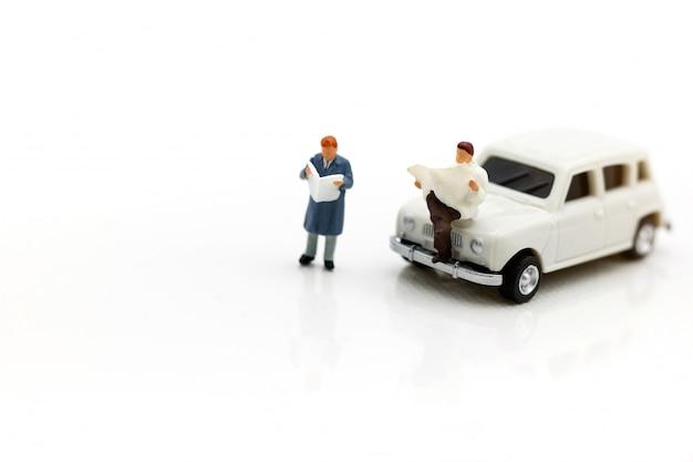 Gente miniatura che legge e che si siede sull'automobile facendo uso del concetto del fondo, di istruzione o di affari.