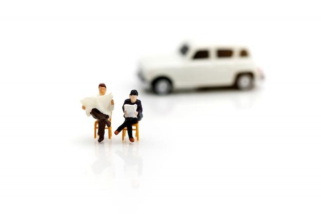 Gente miniatura che legge e che si siede sull'automobile usando come fondo, concetto di istruzione.