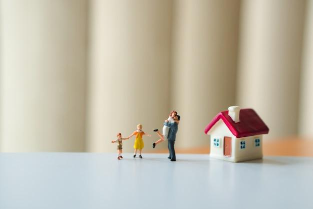 Gente miniatura, famiglia felice che sta con la mini casa facendo uso di come concetto