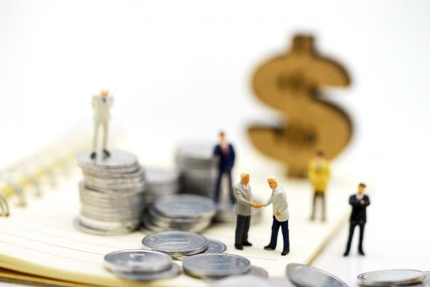 Gente miniatura, uomini d'affari che stanno con la pila delle monete, finanza e concetto di investimento.