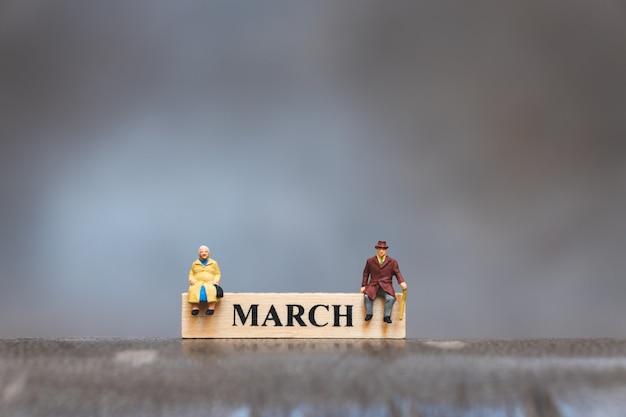 Gente miniatura, uomo anziano e donna che si siedono sul calendario di legno di marzo