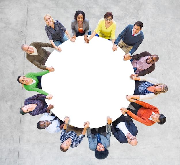 Gente multietnica che forma un cerchio che si tiene per mano