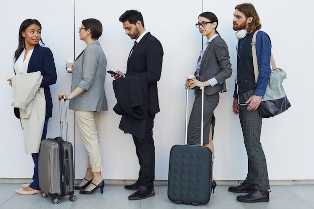 Gente multietnica con bagagli in fila