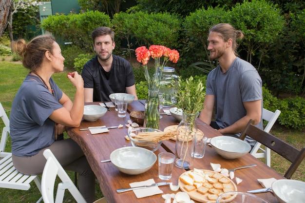 Gente positiva che ha pasto alla tavola di legno in cortile