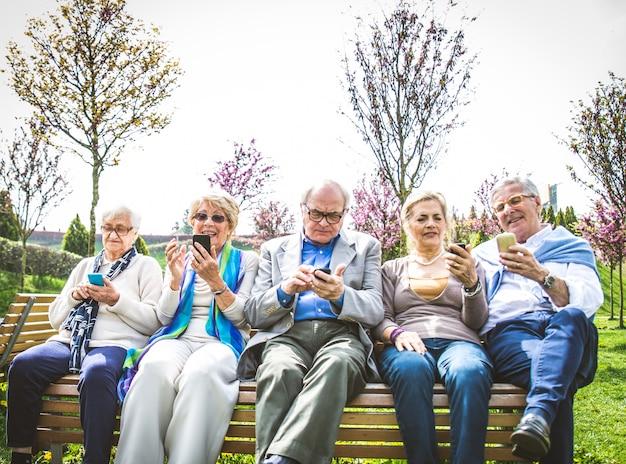 Gente senior che guarda gli smartphone