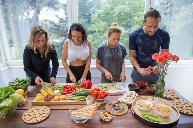 Gente sorridente che cucina le verdure in cucina