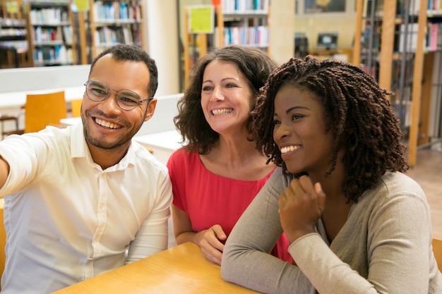 Gente sorridente che posa per l'autoritratto alla biblioteca