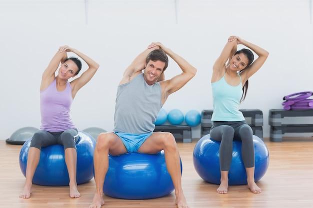 Gente sportiva che allunga le mani sulle palle di esercizio in palestra