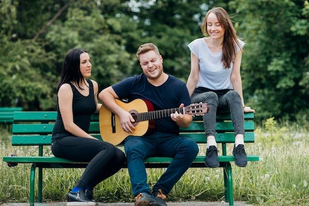 Gente unita che si rilassa sul banco cantando e suonando la chitarra