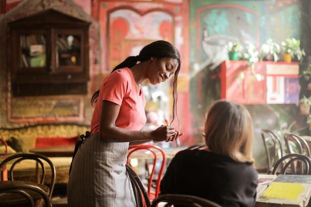 Gentile cameriera afro con un ospite