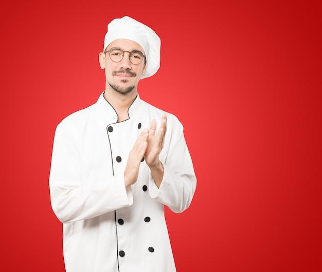 Gentile giovane chef applaudire gesto