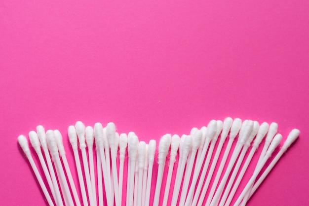Germogli di cotone su sfondo rosa.
