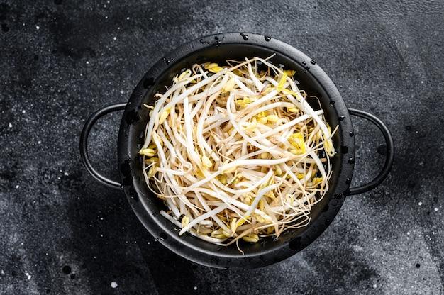 Germogli di fagioli germogliati in uno scolapasta. cibo vegetariano. spazio nero. vista dall'alto