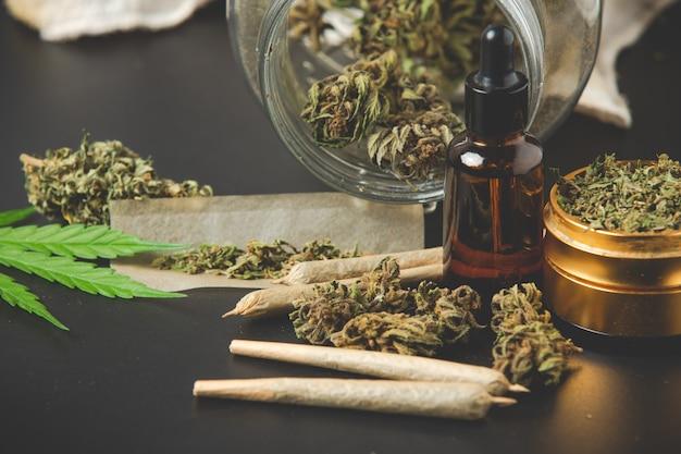 Germogli di marijuana con giunti di marijuana e olio di cannabis