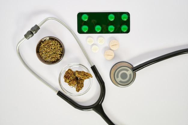 Germogli e smerigliatrice di marijuana con marijuana a terra accanto a uno stetoscopio e alcune pillole su una priorità bassa bianca