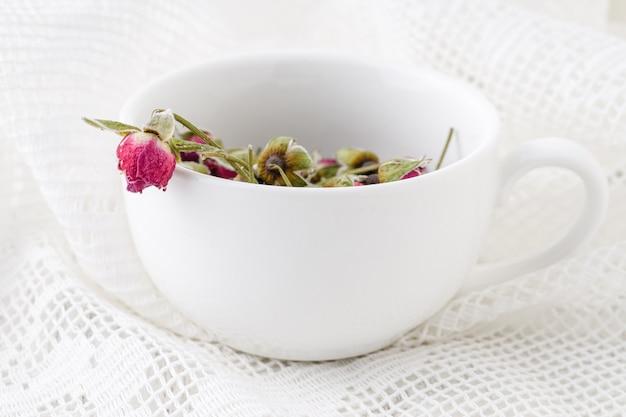 Germogli rosa del tè del fiore sulla vecchia tavola di legno