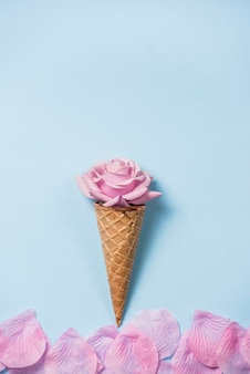 Germoglio di rosa nel cono di cialda sul tavolo