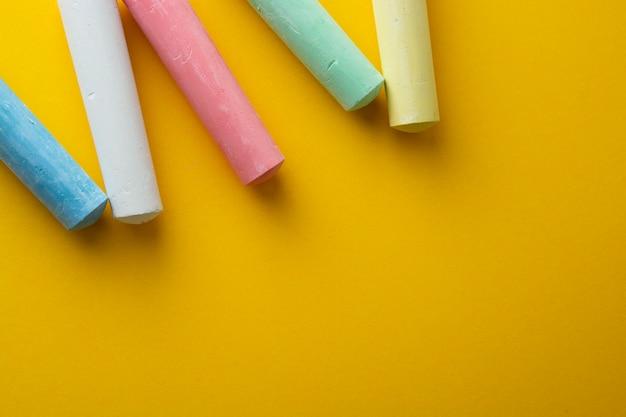 Gessi colorati su sfondo giallo con spazio di copia.