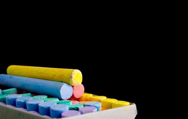 Gessi multi colore su sfondo nero per lo spazio della copia