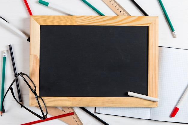 Gesso bordo nero, vetri e gesso sul tavolo bianco, copia spazio.