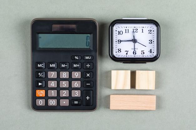 Gestione del tempo e concetto di contabilità con la lente, i blocchi di legno, il calcolatore e l'orologio sulla vista superiore del fondo grigio. immagine orizzontale
