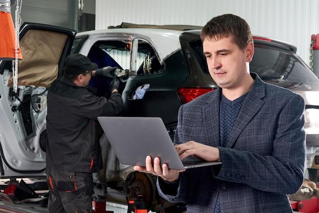 Gestisca il computer portatile della tenuta mentre stanno l'automobile vicina stante nell'officina riparazioni automatica con il meccanico che ripara l'automobile su fondo