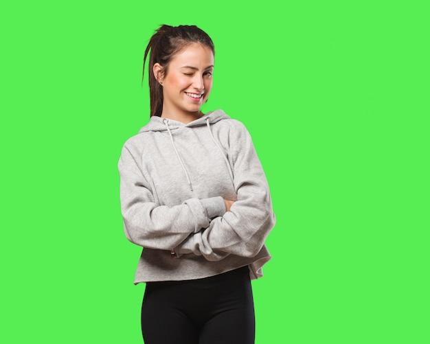 Gesto ammiccante, divertente, amichevole e spensierato della giovane donna fitness
