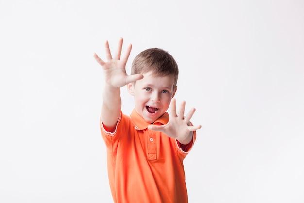 Gesto di arresto di rappresentazione del ragazzino con il fondo bianco eccessivo aperto della bocca