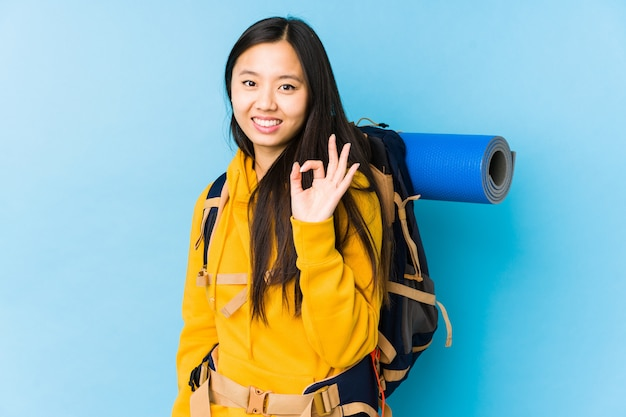 Gesto giusto di mostra allegro e sicuro della giovane donna cinese di viaggiatore con zaino e sacco a pelo.
