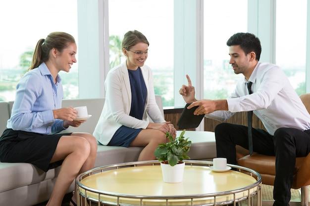 Gestore maschile che mostra il touchpad ai colleghi felici
