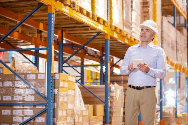 Gestore maschio intelligente che tiene un tablet mentre si effettua un controllo di sicurezza nel magazzino