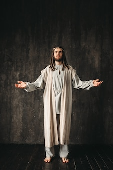 Gesù cristo in veste bianca che prega a braccia aperte. figlio di dio, fede cristiana