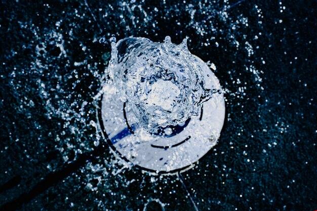 Getto d'acqua salendo verso la telecamera, i toni del blu, sfondo per il concetto idrologico.